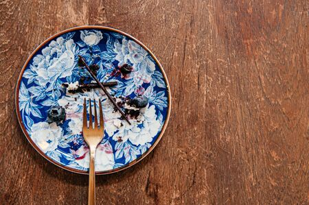 Blueberry cheese cake already eaten left some stain on beautiful luxury ceramic dish with brass fork on wood table Reklamní fotografie