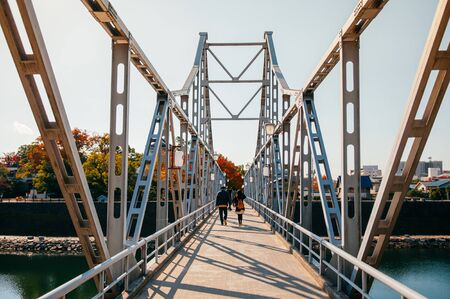 Local Japanese tourists walking on old Iron bridge crossing Asahi river at Okayama castle Reklamní fotografie