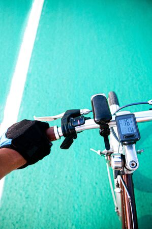 View from bicycle rider hand grabed handle bar during cycling in speed motion. Crop sport bicycle break lever and gear shifter shot Reklamní fotografie