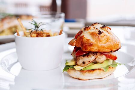 American style Grilled prawn burger with Avocado Aloli sauce and tomato in crispy baked bun in white plate Reklamní fotografie