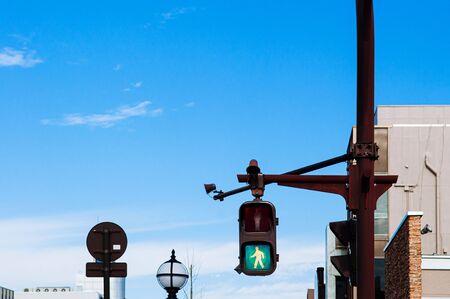 Street green light, crosswalk traffic light at pedestrain crossing with blue sky