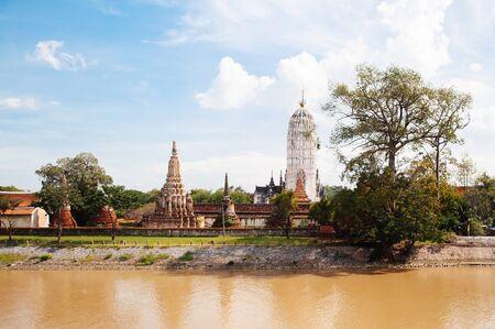 Ayutthaya ancient Buddhist pagodas among ruined brick wall of Wat Putthaisawan historic Temple and Chao Praya River - Thailand. Reklamní fotografie
