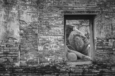 Ayutthaya ancient ruined Buddha statue seen through window frame on brick wall of Wat Putthaisawan temple - Thailand