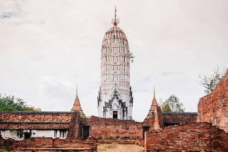 Ayutthaya ancient Buddhist pagoda among ruined brick wall of Wat Putthaisawan historic Temple - Thailand.