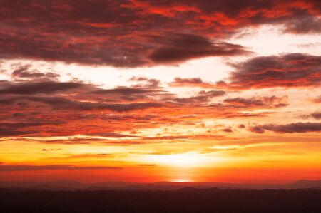 Beautiful summer red vibrant burning sunset or sunrise sky with clouds and mountain range