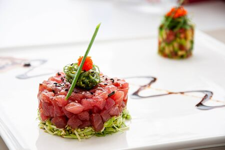 Fresh Tuna tartare sesame seaweed and green salad and balsamic reduction sauce and tropical fruits salsa in white plate