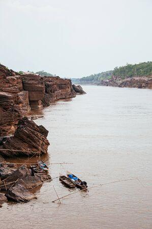 Large Sand stone canyon cliff shoreline of Mekong river and local Thai fishing boat at Ban Pha Chan, Ubon Ratchathani, Thailand.