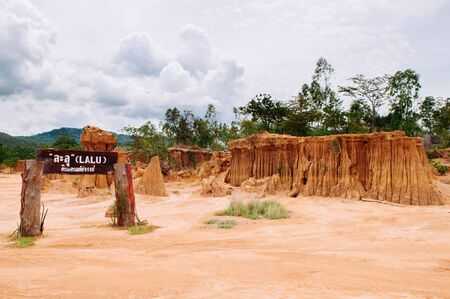 Canyon cliff and desert land of Soil retrogression and degradation at Lalu in Sakaeo, Thailand. Name on wooden sign translated to