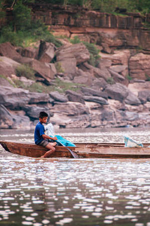 MAY 17, 2010 , Ubon Ratchathani, Thailand - Local Young Thai fisherman and fishing net on old wooden boat in Mekong river, simple and charming Southeast Asia rural life of Indochina region