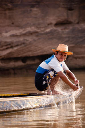 MAY 17, 2010 , Ubon Ratchathani, Thailand - Local Thai fisherman and fishing net on old wooden boat in Mekong river, simple and charming Southeast Asia rural life of Indochina region Editorial