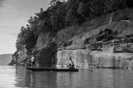 MAY 17, 2010 , Ubon Ratchathani, Thailand - Large Sand stone canyon cliff shoreline of Mekong river and local Thai fishermans at Ban Pha Chan. Black and White Editorial