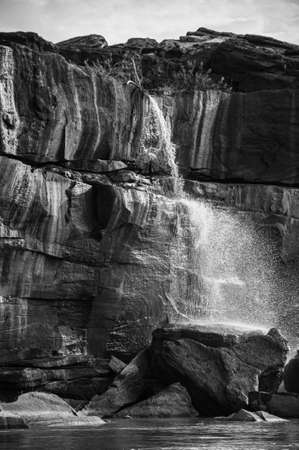 MAY 17, 2010 , Ubon Ratchathani, Thailand - Large Sand stone canyon cliff shoreline and waterfall pouring onto Mekong river with blue sky at Ban Pha Chan. Black and white Editorial
