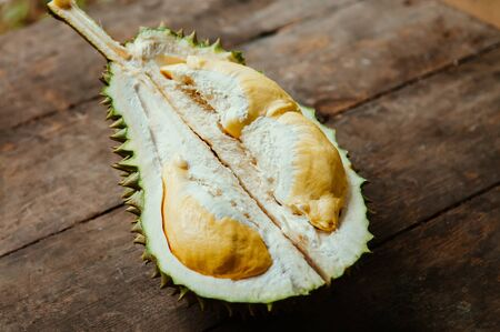 Fresh smelly yellow Durian fruits half cut open on old wood background. King of fruit with spike and unique smell Foto de archivo