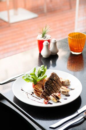 Sea bass fillet steak with grill potato and reduced balsamic sauce in white plate on black stone table.