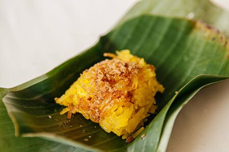 Sweet Shrimp and shred coconut on yellow sticky rice, Traditional Thai local desserts wrapped in banana leaf