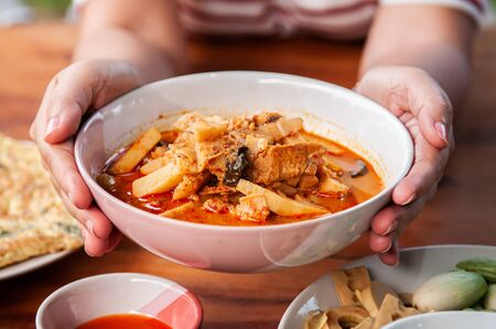 Woman hands holding a bowl of Thai local homemade food red curry with chicken in ceramic bowl at dinner table