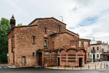 Red brick vintage building of Ca l'Ordal house in La Colonia Guell near Gaudi Crypt