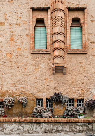 Red brick vintage building and plant pot garden of Ca l'Ordal house in La Colonia Guell near Gaudi Crypt 写真素材