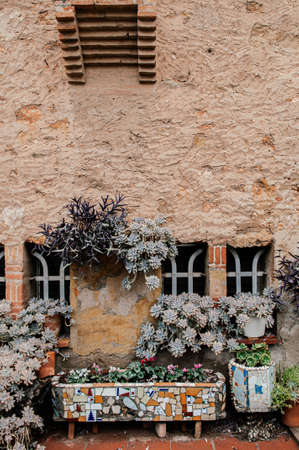 Red brick vintage building and plant pot garden of Ca l'Ordal house in La Colonia Guell near Gaudi Crypt Imagens