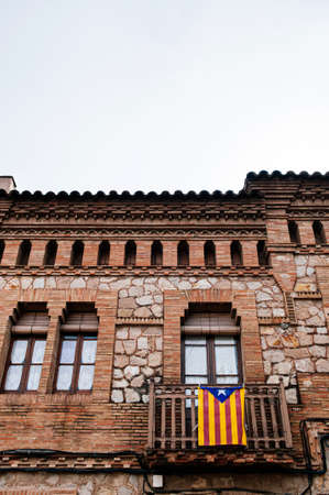 Red brick vintage building with Catalan flag hanging from balcony in La Colonia Guell near placa Joan Guell 写真素材