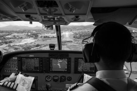 SEP 22, 2011 Pai, Thailand. Pilots in the cockpit during a flight with commercial airplane. Landing with runway scene in valley. Black and white