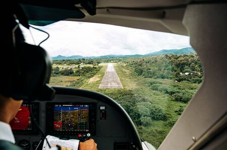 Pilots in the cockpit during a flight with commercial airplane. Landing with runway scene in valley. Pai, Thailand.