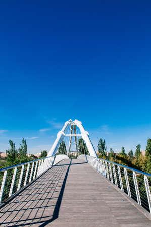 Valencia, Spain - White suspension bridge in Valencia Bioparc under blue sky in autumn