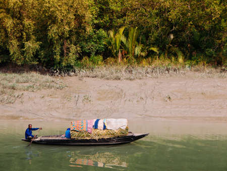 FEB 15, 2012 Dhaka, Bangladesh - Bangladesh local people on wooden row boat in river with tropical mangrove forest. Poverty social in South Asia