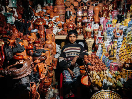 FEB 12, 2012 Dhaka, Bangladesh - Local vintage pottery shop in Dhaka city market with young male seller sit among pots and jars.