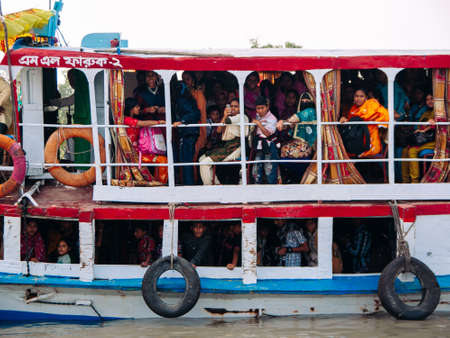 FEB 15, 2012 Dhaka, Bangladesh - Many Bangladesh people riding on commuter river ferry boat in Dhaka. Poverty social in South Asia Publikacyjne