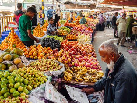 FEB 11,2012 Dhaka, Bangladesh - Bangladesh local tropical fruits market in Dhaka city with buyers and sellers among piles of colourful fruits Publikacyjne