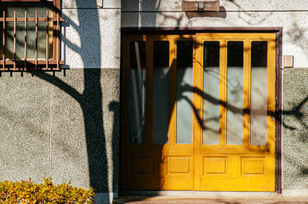 DEC 2, 2018 Hakodate, JAPAN - Vintage colourful yellow houses door under sunlight high contrast shadow and leafless tree in front of entrance