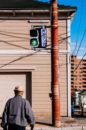 DEC 2, 2018 Hakodate, JAPAN - Japan Street traffic green light at pedestrain crossing with senior people walking with residential building background