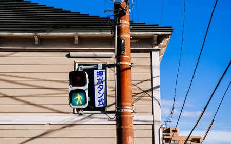 DEC 2, 2018 Hakodate, JAPAN - Japan Street traffic green light at pedestrain crossing with residential building background  under bright winter sunlight
