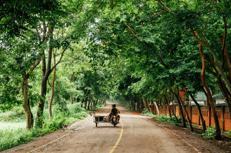 MAY 31, 2018 Sa Kaeo, Thailand - Lush fresh green tree tunnel and peaceful paved street with local people riding one Asain tricycle Publikacyjne