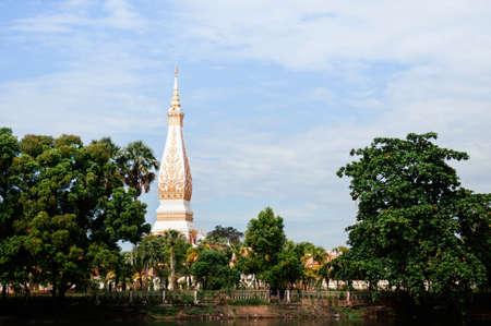 Grand ancient pagoda of Wat Phra That Phanom among big tree and lake, most sacred temple of Nakhon Phanom - Thailand