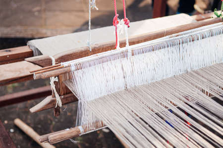 Cotton weaving loom with natural coloured threads local Thai cotton fabric making industry in rural area