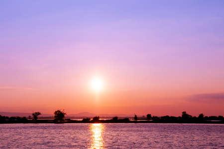 Colourful vibrant sunset over lake at Nong Han Sakon Nakhon - Thailand. Peaceful twilight scenery aginst sunset