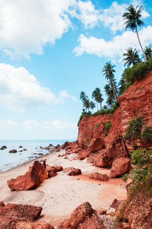 Beautiful tranquil tropical island red cliff rock beach with blue sky and clouds in summer, tranquil serene ocean scenery. Fang Daeng in Prachuap Khiri Khan. Thailand