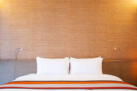 Modern hotel room with white clean linen, pillows and comfort cozy bed with reading lamps.