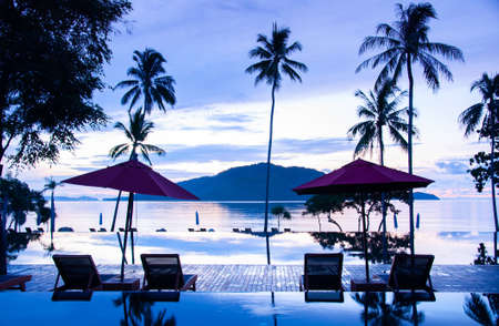 MAY 23, 2010 Phuket, Thailand - Infinity edge pool under morning blue sky in summer with beach umbrellas and ocean view in tropical island resort in Phuket.
