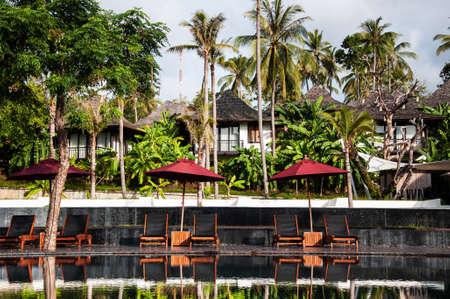 MAY 23, 2010 Phuket, Thailand - Infinity edge pool under blue sky in summer with beach umbrellas in tropical island resort in Phuket.