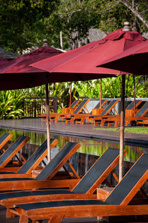 Beach beds at infinity edge pool in summer with red umbrellas in tropical island resort in Phuket. Stock fotó