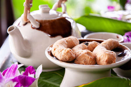 Afternoon tea in ceramic pot and butter cookies among flower and green leaves table decoration