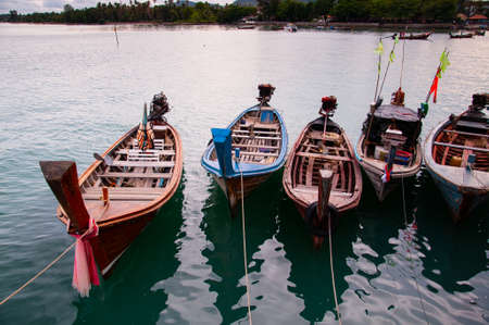 Colorful longtail fishing boat in small canal during monsoon season in Phuket
