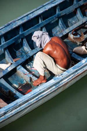JUN 5, 2010 Phuket, Thailand - Local Fisherman with beautiful tanned skin in longtail fishing boat at Chalong bay