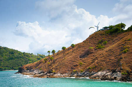 Golden grass cape and blue sea under blue sky with white clouds at Yanui beach in phuket. Thailand