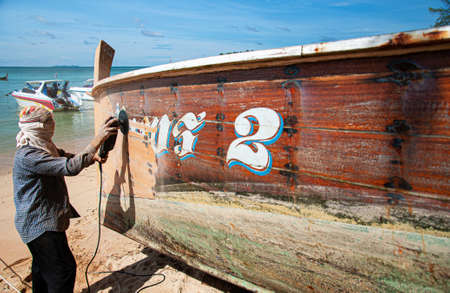 JUN 5, 2010 Phuket, Thailand - Thailand Local Fisherman fix and repair wooden longtail fishing boat with tool at on the beach of Chalong bay Редакционное