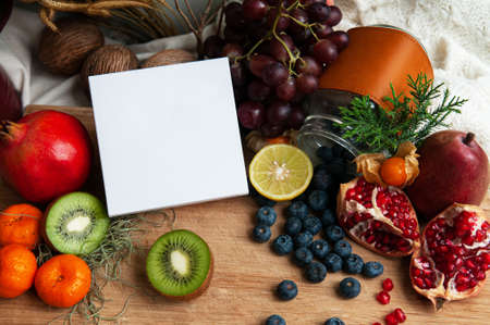 Blank white box packaging among colourful fruits, berries, kiwi, pomegranate and citrus. Dietary supplement packaging box. 写真素材