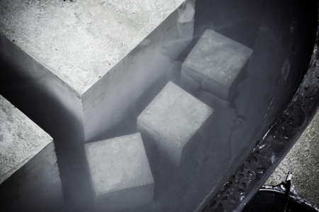 Concrete cube blocks for concrete strength testing soak in water tub for curing process.
